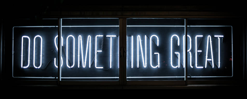 """Photograph of a neon text stating """"do something great"""" by Clark Tibbs."""