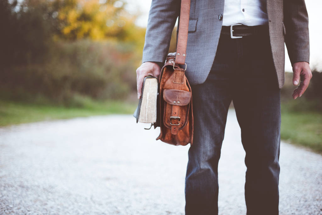 A walking man with a leather bag and an old book.
