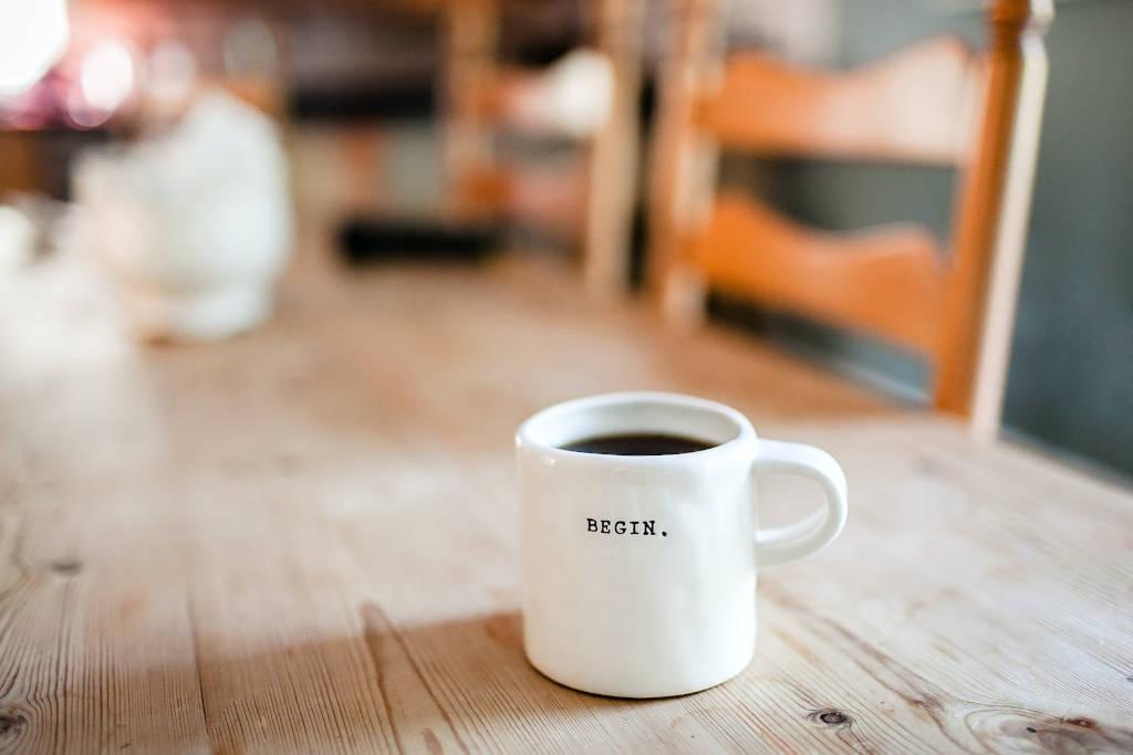 """Fang an. Eine Kaffetasse mit der Beschriftung """"Begin."""" auf einem aufgeräumten, warm wirkenden Tisch."""