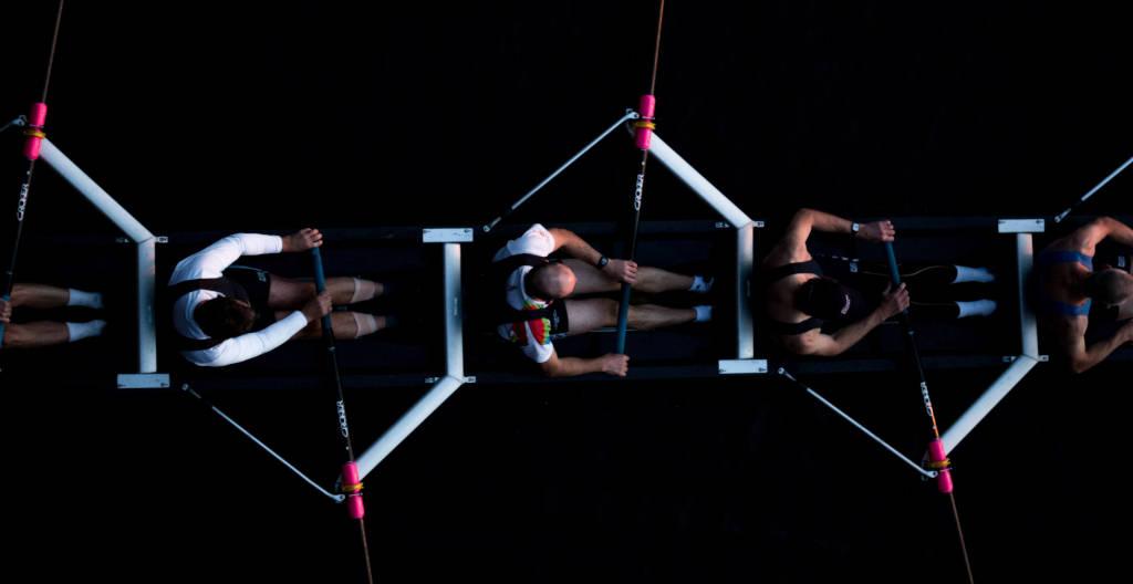 Five men riding a row board, photo by Josh Calabrese